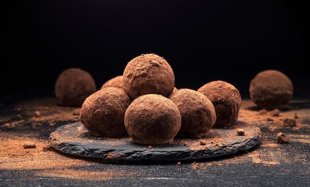 Chocoladetruffels, ronde chocoladesuikergoed op zwarte leiachtergrond met cacaopoeder