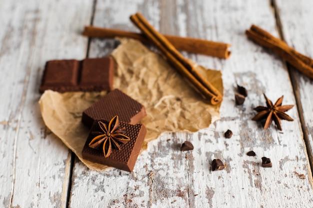 Chocoladevierkanten en pijpjes kaneel op papieren zak