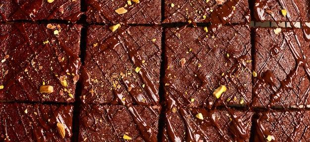Chocoladevierkanten met pistachenoten en aardbeien op een metalen standaard op een lichte stenen achtergrond, bovenaanzicht, horizontale compositie. plat leggen