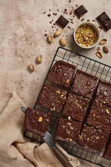 Chocoladevierkanten met pistachenoten en aardbeien op een metalen standaard op een lichte stenen achtergrond, bovenaanzicht, horizontale compositie. plat leggen.