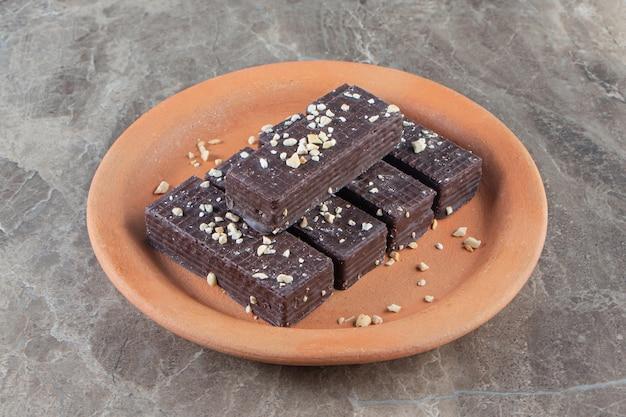 Chocoladewafel op een kleiplaat op marmer.