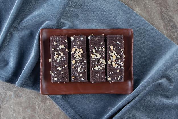 Chocoladewafel op een schotel op stukjes stof op marmer.