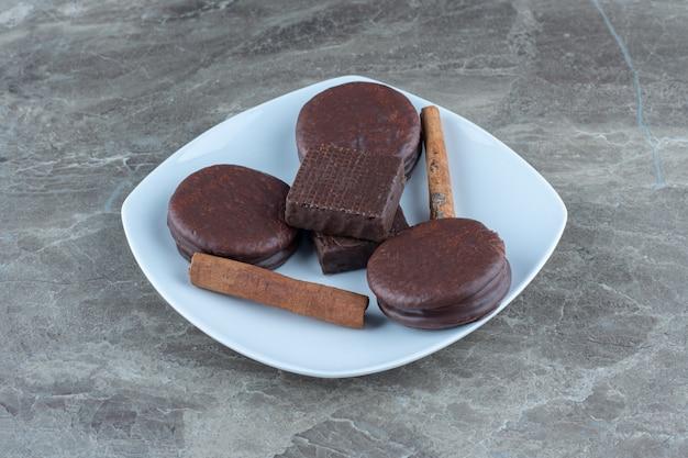 Chocoladewafeltje en koekjes met pijpjes kaneel op witte plaat.
