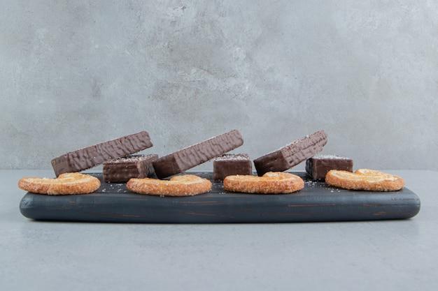 Chocoladewafeltjes en vlokkige koekjes op een zwarte bord op marmeren achtergrond.