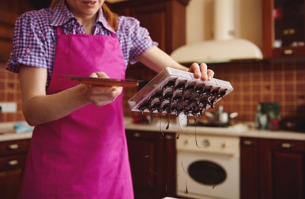 Chocolatier die overtollige chocolademassa verwijdert uit mallen op de marmeren tafel, voor het maken van handgemaakte chocoladepralines.