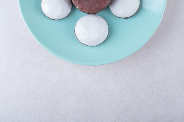 Cholaat gecoat cookie mini mousse gebak dessert op een bord op marmeren tafel.