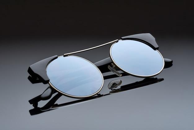 Chor metalen glazen met ronde spiegelglazen liggen op het reflecterende oppervlak.