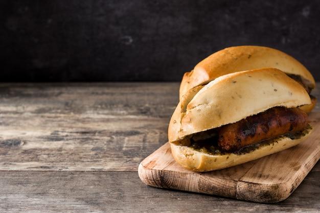 Choripan. de traditionele sandwich van argentinië met chorizo en chimichurrisaus op de houten ruimte van het lijstexemplaar
