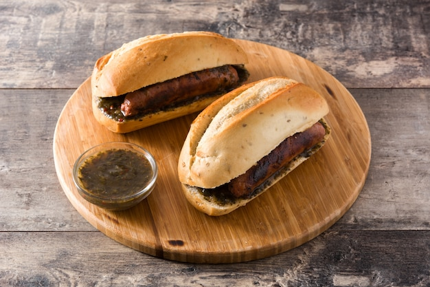 Choripan. de traditionele sandwich van argentinië met chorizo en chimichurrisaus op houten lijst