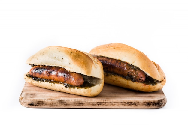 Choripan. traditionele argentijnse sandwich met chorizo en chimichurrisaus. geïsoleerd op wit
