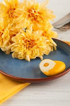 Chrisanthemum-bloemen op een plaat op een houten lijst