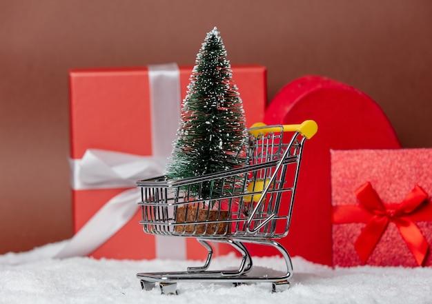 Chrismtasboom in een kar met geschenkdozen