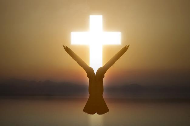 Christelijk kruis en silhouet van duif met een achtergrond van de zonsopganghemel