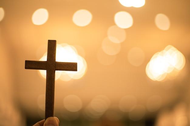 Christelijk kruis met vaag bokehlicht als achtergrond bij kerk.