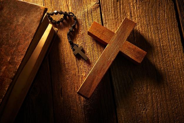 Christelijk kruis op houten bijbel en rozentuin