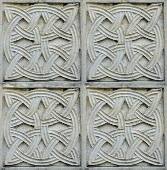 Christelijk patroon gesneden in steen op de muur van een oude christelijke kerk in georgië