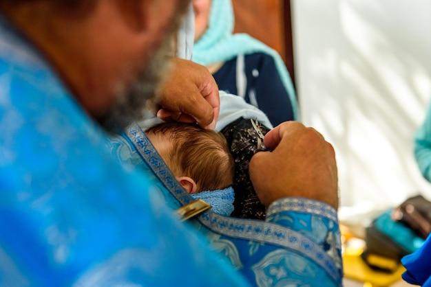 Christelijke doopritueel van een kind in een kerk, een priester zalft de wereld met een been van een klein kind