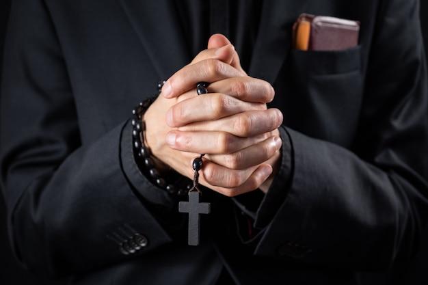 Christelijke persoon die bidt, rustig beeld. handen van een man in zwart pak of een priester die een prediking afbeeldt