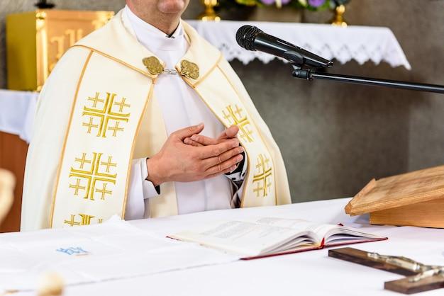 Christelijke priester die bij het altaar staat.