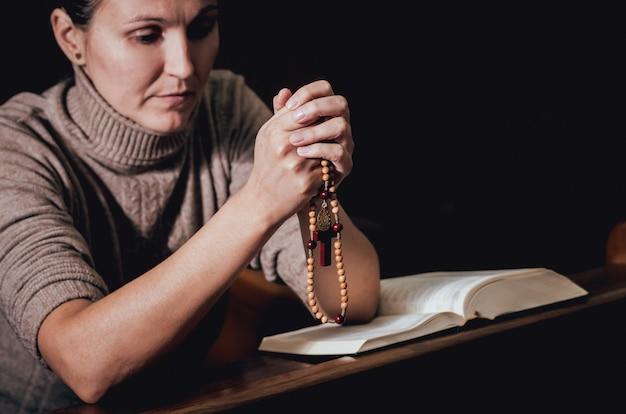 Christelijke vrouw bidden in de kerk. gekruiste handen en bijbel op houten bureau.