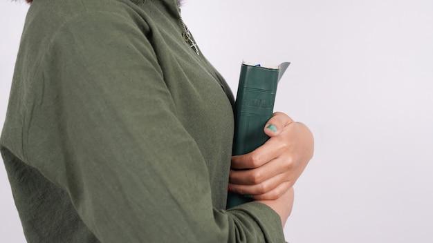 Christelijke vrouwen houden de geïsoleerde witte muur van de schrift vast