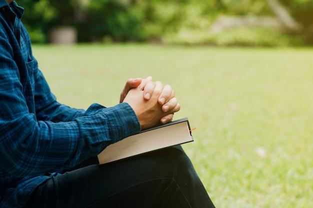 Christenen en bijbelstudie concept. jonge man zit en gebed op bijbel. kopie ruimte