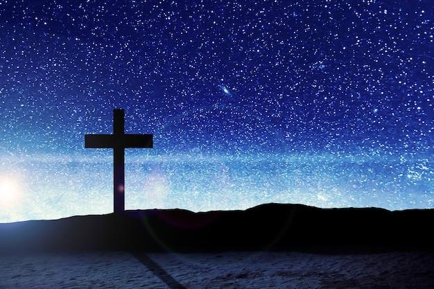Christian cross op het veld met de achtergrond van een nachtscène