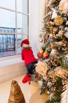 Christmas child elf in santa hat, elf. prettige kerstdagen en fijne feestdagen. klein meisje bij het raam zitten en kijken naar het winterbos.