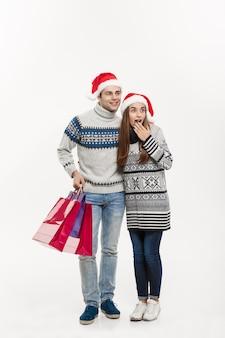 Christmas concept - full length jonge aantrekkelijke paar bedrijf boodschappentassen geïsoleerd op wit grijze muur.