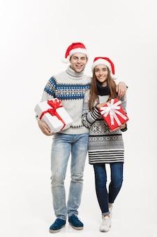 Christmas concept - jonge schattige paar bedrijf presenteert geïsoleerd op wit grijze muur.