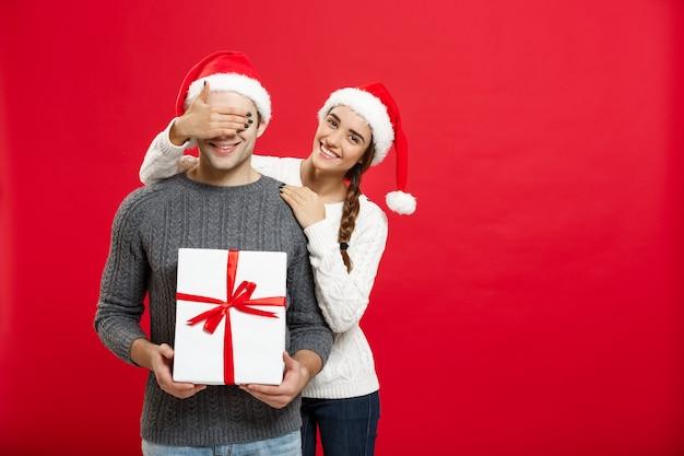 Christmas concept - jonge vrouw die de ogen van de man behandelt met de hand en een groot verrassingsgeschenk geeft. geïsoleerd op rode muur.