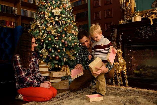 Christmas family open present gift bag, op zoek naar magisch licht in het interieur van de kerstboom