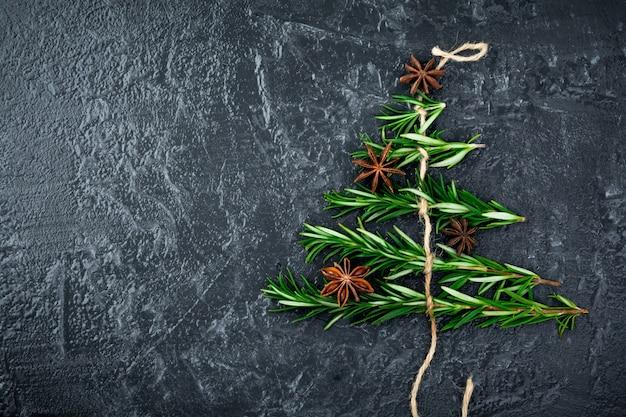 Christmas food.christmas boom van rozemarijn en anijs op een zwarte plaat. plaats voor tekst.