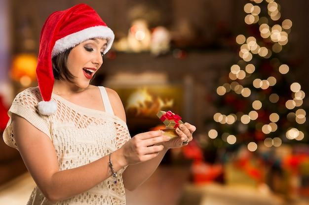 Christmas gift - vrouw openen geschenk verrast en blij, jonge mooie glimlachende vrouw in santa hat.
