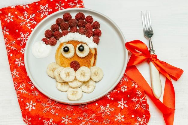 Christmas santa claus vormige pannenkoek met zoete verse frambozen bessen en banaan op plaat op witte houten achtergrond voor kinderen kinderen ontbijt. xmas eten met nieuwjaarsversieringen.