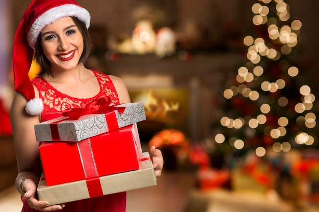 Christmas santa hat geïsoleerde vrouw portret houden kerstcadeau. glimlachend gelukkig meisje over kerstmisachtergrond