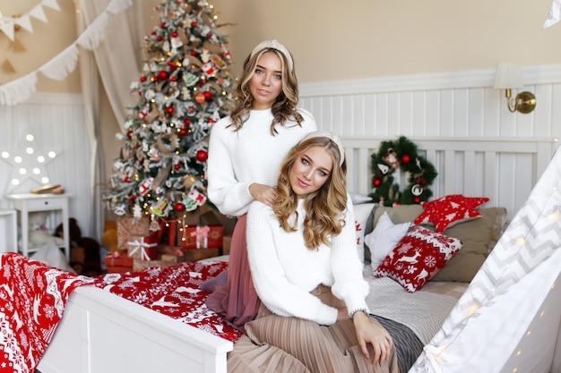 Christmas shooting concept, twee gelukkige lachende meisjes vrienden tweeling zus in de slaapkamer bij de boom