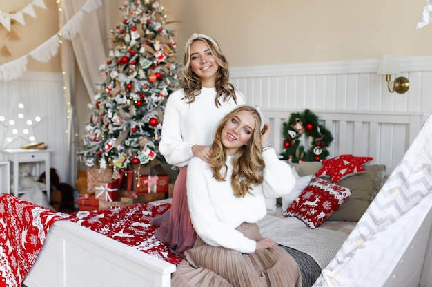 Christmas shooting concept, twee gelukkige lachende meisjes vrienden zus in de slaapkamer bij de boom