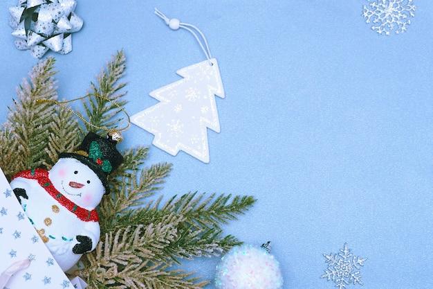 Christmas speelgoed sneeuwpop in een hoed kunstmatige vuren takken, kerstboom beeldje, zilveren sneeuwvlokken, strikken en spiraal lint op een blauw-grijze achtergrond.