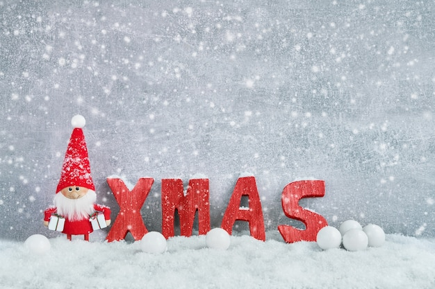 Christmas wenskaart. de achtergrond van de kerstmangnoom met kerstmisdecoratie en sneeuw. kerst symbool