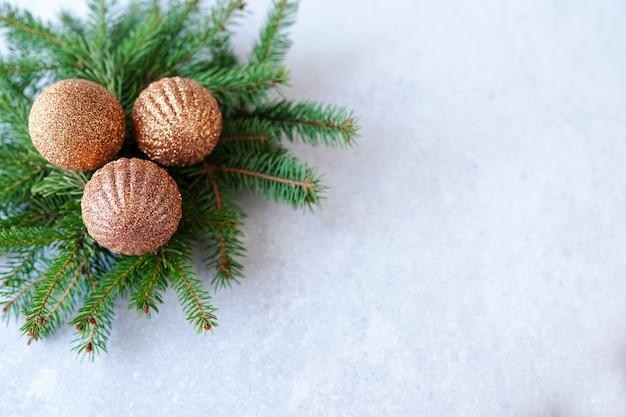 Christmas wenskaart met fir takken en gouden ballen decoraties op lichtgrijze stenen achtergrond met kopie ruimte