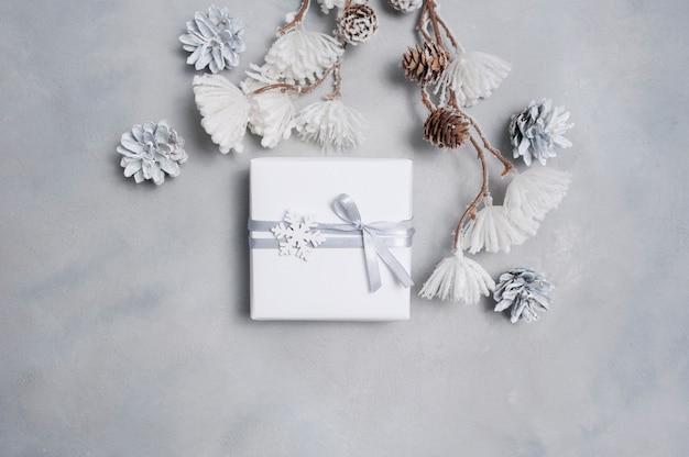 Christmas wenskaart met geschenkdoos, kegels en sneeuwvlokken