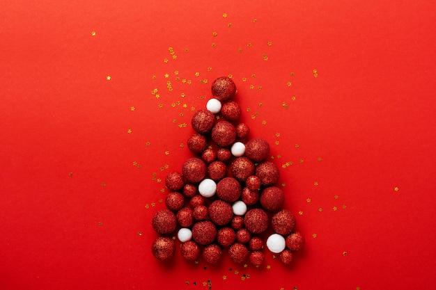 Christmas wenskaart met kerstboom gemaakt van rood speelgoed ballen ingericht gouden confetti in rode envelop op rood.