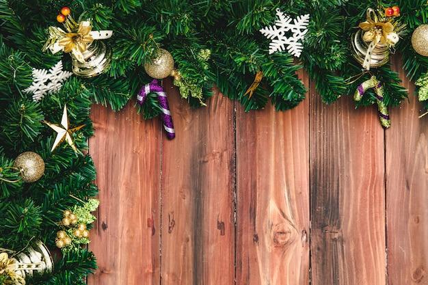 Christmast en nieuwjaarsviering concept, dennentakken aan de rand versieren met mooie ornamenten. gezet op natuurlijk houten bord. lege ruimte in het midden, bovenaanzicht.
