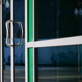 Chromen deurklink en glas van moderne aluminium kantoorgevel
