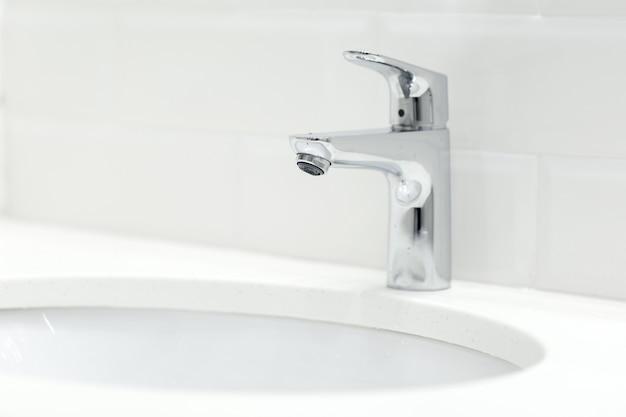 Chromen kraan op de keramische wastafel in de badkamer