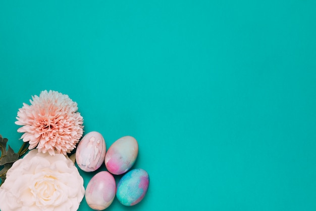 Chrysant; roos en beschilderde paaseieren op de hoek van de groene achtergrond