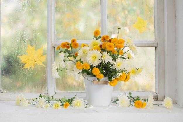 Chrysanten in vaas op vensterbank in de herfst