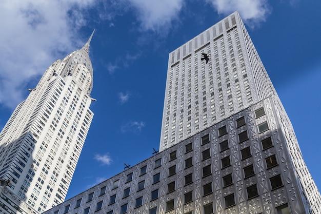 Chrysler building en een wolkenkrabber tegen het blauwe luchtsilhouet van de vliegende vogel