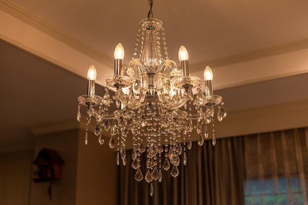 Chrystal kroonluchterlamp aan het plafond in de eetkamer het beeld aanpassen in een luxe toon. decoratief elegant vintage en eigentijds interieurconcept.